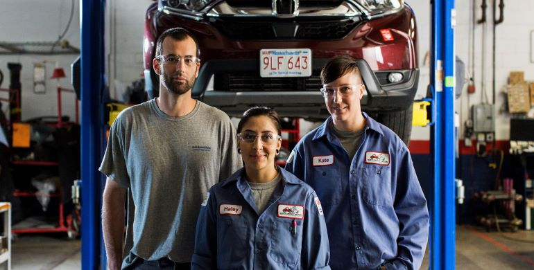 2 females and 1 male car mechanic in an auto repair shop